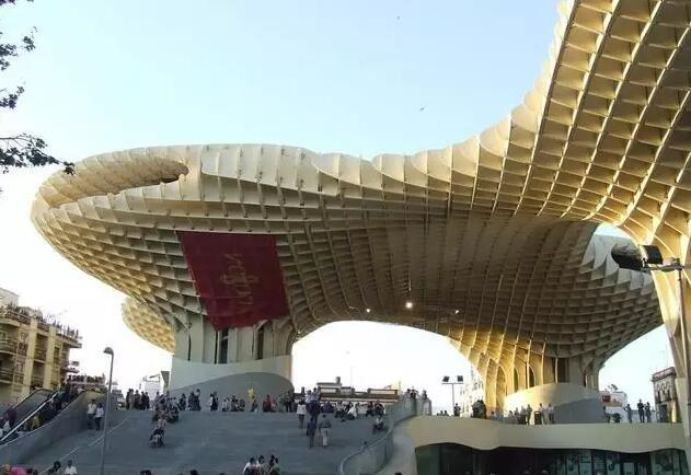 从天而降,抑或是拔地而起?这是位于西班牙古城塞维利亚的一座巨型木结构建筑,由波从动起伏的木板组合而成,建筑面积近5000平方米,高度为28.5米,堪称当今世界上规模最大的木结构建筑。从空中俯瞰塞维利亚全景,整个建筑就像一把巨大的都市阳伞,在混凝土枝干下方是宽阔的广场,行人行走其间畅通无阻,还能与巨大的网格投影玩游戏。  该建筑名为Metropol Parasol,是塞维利亚Encarnacion广场改造项目的主体工程,由著名的柏林建筑事务所J.