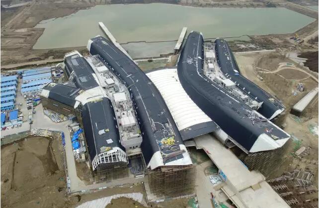 国家海洋博物馆是我国首座国家级、综合性、公益性的海洋博物馆,是中华民族海洋文明的代表性博物馆,被誉为海洋上的故宫。作为项目承建方,中建八局建造的不仅是天津滨海新区的文化地标,更是中国海洋事业的文化里程碑。  精细解构:轻松转化异形难题 国家海洋博物馆项目由四大场馆和中央大厅组成,钢结构总用钢量约为2万余吨,主体钢结构采用异形超高大跨度门式管桁架-框架组合体系,门式桁架分布于四大场馆并排设置,在空中通过桁架间支撑杆件相互连接,使建筑整体外形呈现四条鱼跃造型。  这个项目整个体系共有门桁架112榀,单