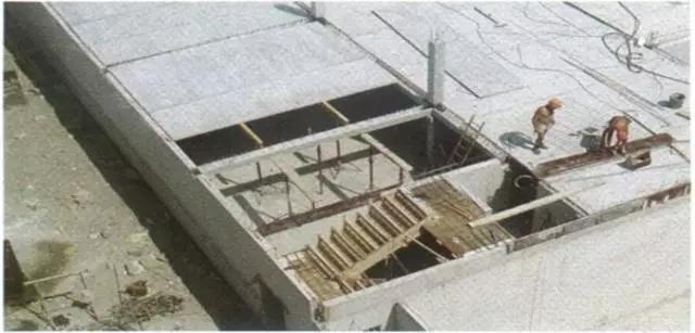 法国PPB技术的主要制品 法国PPB技术经历了不同的发展阶段。目前的产品体系包括预应力混凝土(PC)梁、PC板、SCOPE体系(多层建筑)、预制PC楼梯、PC壳屋面、PC窗框架,如图1所示。  图1 法国PPB技术的主要制品 1、空心板 十多年前空心板就是应用最广泛的预制楼板,其优点主要是具有高效的设计和生产方法、方便合理的构件厚度和承载力、面层选择及较高的结构效率。空心板同样具有大跨度的工作能力,能很好地满足灵活性和适应性的要求。目前厚400mm、跨度17m、承受5kN/m2活载的空心板已得到广泛应用。